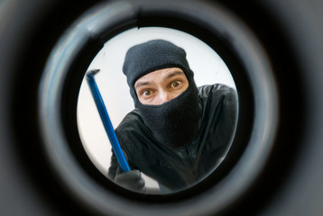 View through pipehole. Thief or burglar masked with balaclava is holding crowbar behind the door.