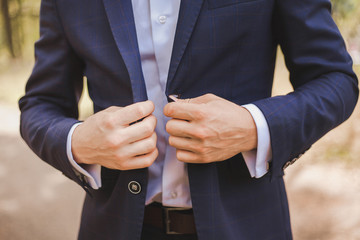 Young handsome stylish man dressed in modern formal clothes buttoning jacket. Close up of hands of guy in blue jacket, violet shirt. Person ready for wedding celebration or graduation.