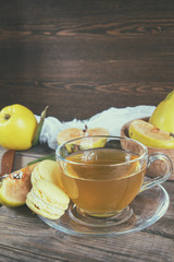 The cup of hot  tea and fresh quince fruit on dark wooden table. An autumn still life. Coloring and processing photo