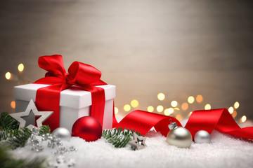 Weihnachten Hintergrund mit Geschenk und rotem Band, Lichtern, Kugeln, Tannenzweigen und Schnee