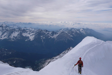 a mountain climber on an exposed ridge in the Swiss Alps