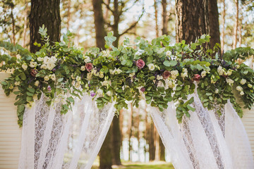 Beautiful outside floral decoration for wedding ceremony in scenic place in old wood. White arch decorated with bright fresh flowers and white fabric. Color horizontal photo.