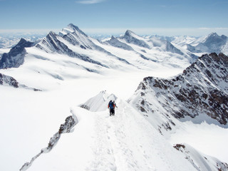 mountain guide and client descending a high alpine peak with a gigantic panorama of the Swiss Alps
