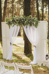 Beautiful outside decor for wedding ceremony in scenic place in old wood. White arch decorated with fresh flowers and rows of many wooden chairs. Color horizontal photo.