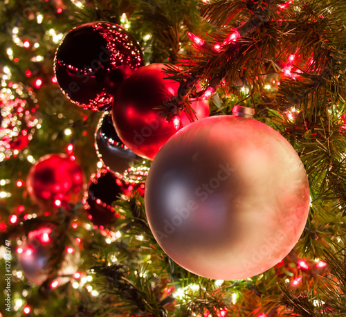 close up of pink and red ornaments on a large christmas tree lit with red and