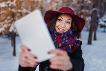 Beauty young happy woman in warm winter clothes taking selfie photo using tablet