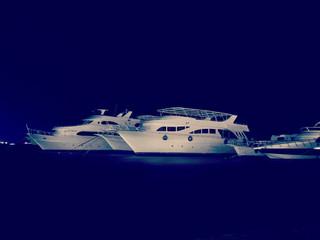 Diving safari yachts at night marina, retro hipster style