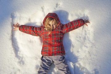 A young child playing in the snow making an angle