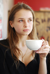beautiful young girl with a cup of coffee in a coffee shop looki