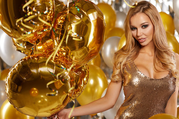 portrait of blond young woman between golden balloons and ribbon
