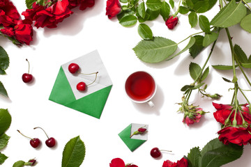 Red tea, ripe cherries, small envelopes with green leaves roses isolated white background. Tea drinking during work. Healing drink. Aromatic morning. Berry compote. Flat lay, top view. Flower frame