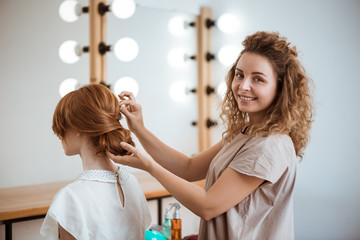 Female hairdresser smiling making hairstyle to redhead girl in beauty salon. Wall mural