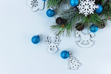 Christmas tree handmade spruce branches with cones blue balloons white background