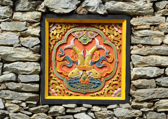Bhutan style carved wood on stone wall