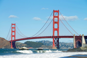 Golden Gate Bridge, viewed from Baker Beach during King Tide phenomenon at high tide with waves crashing over the beach in foreground, blue cloudy sky and Marin hills in background