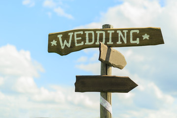 Wedding wooden sign on sky background