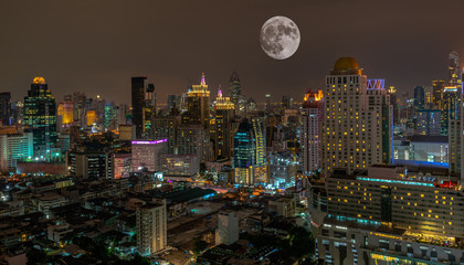 Super full moon above Bangkok city at night , Thailand .