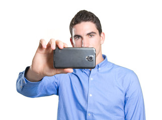 Concentrated young man taking a picture with his mobile