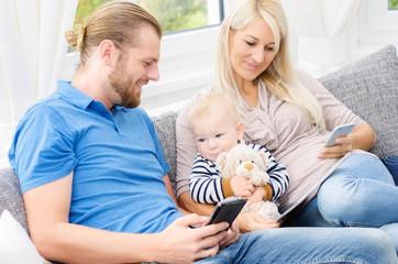 Junge Familie mit Tablett und Handy