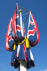 Ceremonial Union Jack British flags hang draped on a pole in bright blue sky along The Mall in London, UK