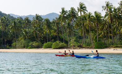 Koh Chang, Thailand MARCH 28, 2015; Tourists kayaking on sunny tropical beach with palm trees