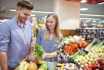 Couple choosing fresh food in supermarket