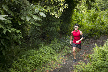 Athletic Chinese man running on forest trail.