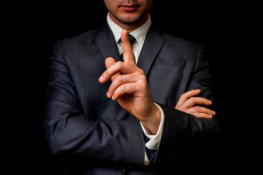 Businessman showing one finger, making silence gesture