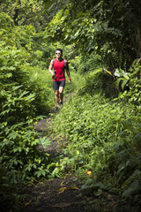 Athletic Chinese man walking on forest trail.