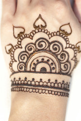 drawing henna patterns on her arm