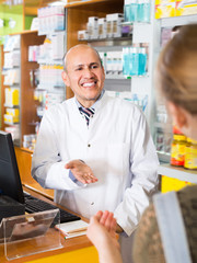 Pharmaceutist helping young woman in drugstore