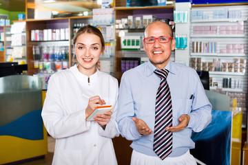 Smiling pleasant pharmacist and pharmacy technician