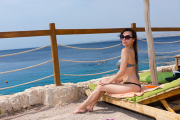 Young slim female in sunglasses sitting on sun lounger, tanning