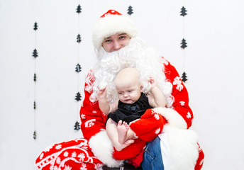 Santa Claus with baby girl in the white room.