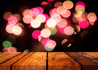 wood table and blurred bokeh colorful lights.