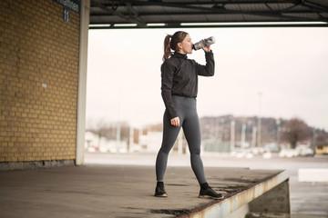 Female runner drinking bottled water on warehouse platform