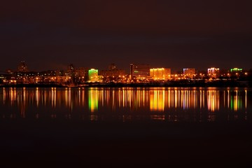evening city landscape with reflection in the ice lake