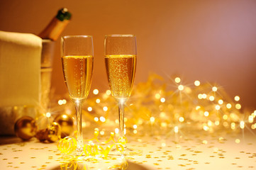 Champagne flutes on table decorated with streamer and gold confe