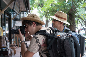 Side view of two backpackers taking a picture and visiting tourist attractions in Bangkok, Thailand