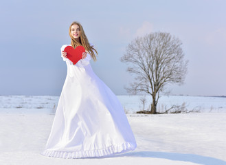 Beautiful young woman holding a red heart in the hands. Winter t