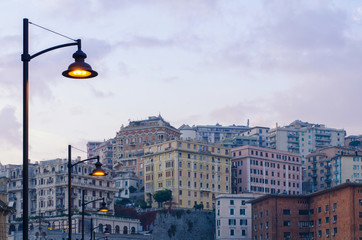 Street lamps lighting up as the evening sets in the residential district of Genoa, San Teodoro, with the architectural panorama visible on the hills of the city