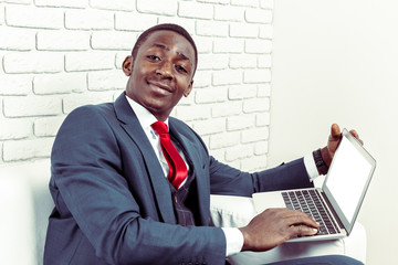 African young man holding laptop