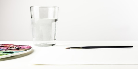 Watercolor brush, palette, glass of water, copyspace
