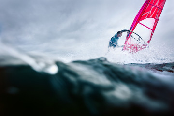 freestyle windsurfer in a huge splash
