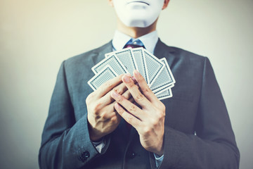 Businessman in mask holding a set of playing cards - hiding expression in business strategic competition concept