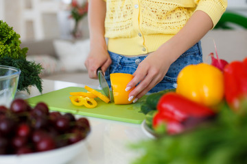 The hands of a young slender woman, clad in a yellow blouse and blue jeans, working on a large bright kitchen,slicing fresh vegetables for the preparation of dietary salad a large kitchen knife