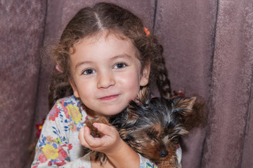 Girl holds puppy in hands
