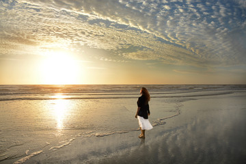 Woman relaxing on the beach at sunrise, beautiful cloudy sky and sun  reflected on beach, Jacksonville, Florida, USA.