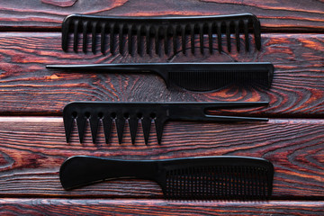 hairdresser combs of different shapes on a wooden background close up