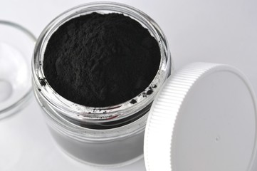 Activated charcoal powder for cosmetic face mask in a jar top view with copy space